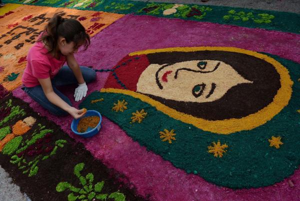 Associated PressA worker helps create the sawdust carpet in Guatemala City, Guatemala on Thursday