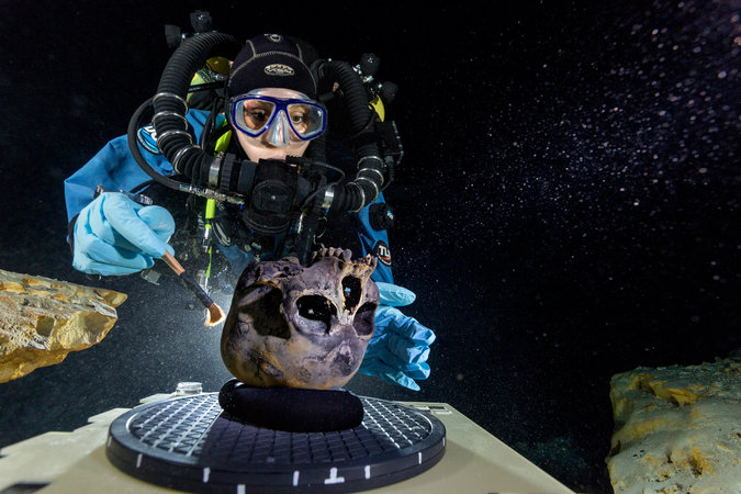 A diver, Susan Bird, cleaning the skull of a prehistoric teenage girl, recently discovered in an underwater cave in Mexico. Credit Paul Nicklen/National Geographic, via Associated Press