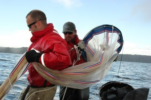 Jed Moore and Emiliano Perez, Nisqually natural resources staff, deploy a plankton net in deep South Sound.