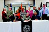 Cherokee Nation Secretary of State Chuck Hoskin Jr., left, and Principal Chief Bill John Baker sign the reimbursement agreement Friday. Next to Baker is James Floyd, the director of the Jack C. Montgomery VA Medical Center. Watching from behind are Gayla Stewart, left, the victim witness coordinator for the regional U.S. Attorney's Office; Dr. Ricky Robinson, the director of the Cherokee Veterans Center; Vickie Hanvey, the Cherokee Nation self-governance administrator; Jacque Secondine Hensley, the Native American liaison for Gov. Mary Fallin; Connie Davis, the executive director of Cherokee Nation Health Services; Tribal Council Speaker Tina Glory-Jordan; Deputy Chief S. Joe Crittenden; and John Alley and Bunner Gray, Indian health liaisons for the VA center.