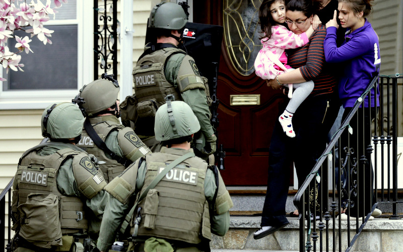 A woman carries a girl from their home as a SWAT team searching for a suspect in the Boston Marathon bombings enters the building in Watertown, Mass., Friday, April 19, 2013. (AP/Charles Krupa)