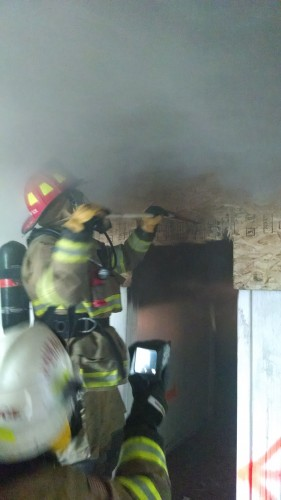 Fireman Eric Brewick punches out portions of the wall for ventilation.Photo: Andrew Gobin/Tulalip News