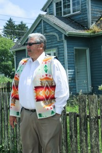 Larry Ralston, Quinault Indian Nation Treasurer, stands in front of his mother's house which will not be moved during the relocation of Taholah's Lower Village, and could face possible demolition along with other buildings that cannot be moved. Photo/ Brandi N. Montreuil, Tulalip News