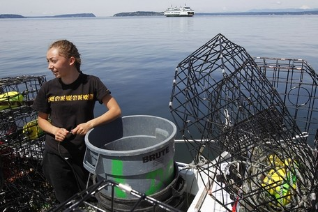 Genna Martin / The HeraldShaylene Jefferson, 16, of Suquamish, waits in the boat for her uncle, in Mukilteo, after a day of crabbing in Puget Sound on June 11.