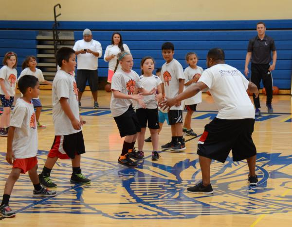 Jack McNeelCoach Lee Adams demonstrates defense as youngsters and other coaches look on.