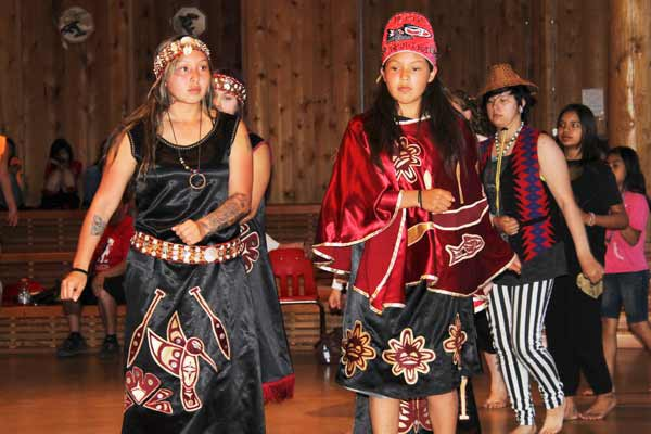 Members of the Nisqually Tribe participate in a paddle dance during protocol, a time of cultural sharing, June 19 in the Port Gamble S'Klallam House of Knowledge longhouse.Image Credit: Richard Walker/ Staff Photo