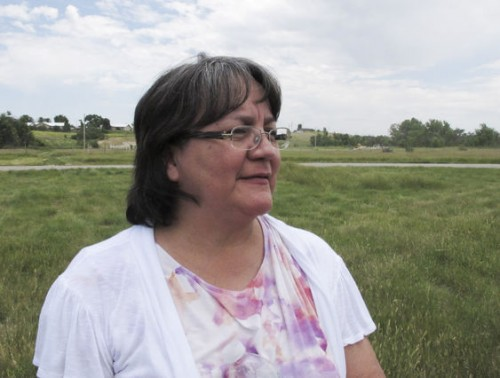 In this July 10, 2014 photo, Denise Mesteth poses outside the powwow grounds in Pine Ridge, S.D. Mesteth is a member of the Oglala Sioux Tribe, born and raised on the Pine Ridge reservation. She has signed up for health insurance through the federal marketplace. (AP Photo/Nora Hertel)