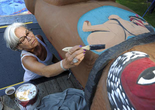 Colin Mulvany photoTotem pole painter and carver Lucy London touches up the paint on a traveling 19-foot totem pole that visited Spokane on Tuesday. The totem pole's 2,500-mile, two-nation journey includes stops in communities impacted by increased coal and oil rail traffic.