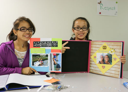 Tatiana Bumgarner is joined by younger sister Priscilla as they show off their summer scrapbook full of photos they have taken during the groups field trips. Photo/ Brandi N. Montreuil, Tulalip News
