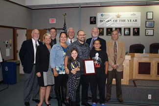"""Christopher AnderssonAnthony Craig (center), co-principal of Quil Ceda Tulalip Elementary, stands with his wife and children next to him and Marysville education leaders behind him after being given the """"Outstanding Young Educator"""" award during the Sept. 2 Marysville School Board meeting."""