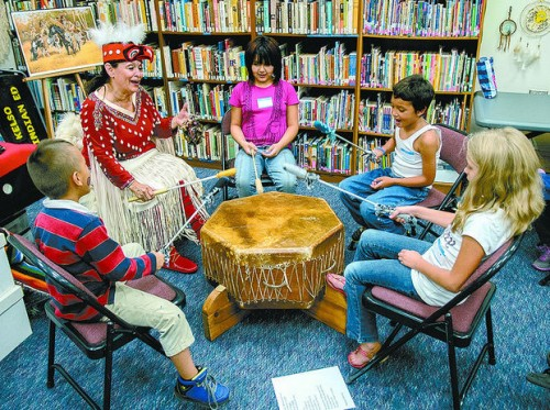 Wallace Elementary students beat on a rawhide drum with LaMere. Photo/ Roger Werth / The Daily News
