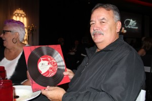 Tulalip artist Joe Gobin holds up one of the menus featuring his artwork.
