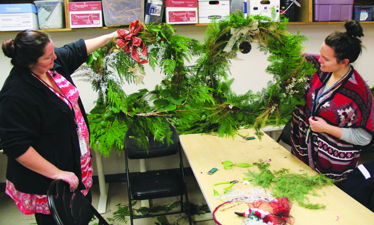 Tribal employees Mietra Williams and Amber Ramos proudly display their handmade wreaths. Photo/Micheal Rios
