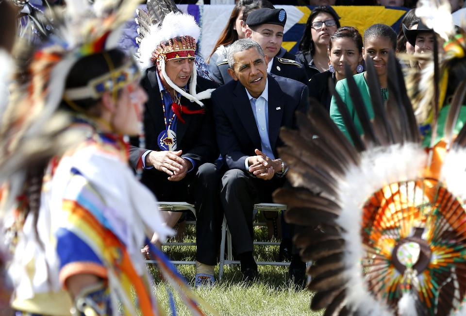 In this June 13, 2014 file photo President Barack Obama and Chairman of the Standing Rock Sioux Tribe David Archambault II, left, watch dancers during a visit to the Standing Rock Indian Reservation in Cannon Ball, N.D. Obama on Wednesday, Dec. 3, 2014 announced an initiative to improve conditions and opportunities for American Indian youth, more than one-third of whom live in poverty. (AP Photo/Charles Rex Arbogast, File)