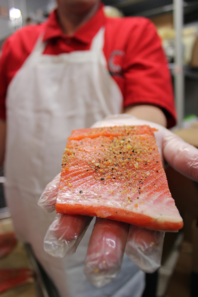 Shawn Saylor, the kitchen coordinator for the Muckleshoot Indian School, holds a piece of salmon to be served at the school.