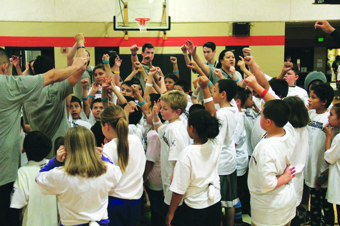 Trainers, volunteers and child participants huddle up to celebrate their evening of physical activity. Photo/ Micheal Rios