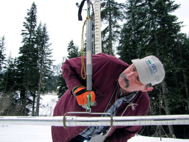 Scott Pattee, a water supply specialist with the National Resources Conservation Service, checks snow levels at Stevens Pass ski resort in Washington's Cascade Mountains. Ashley Ahearn/KUOW