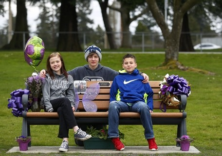 Mark Mulligan / The HeraldGia Soriano's cousins, 11-year-old Gabby (left) and 14-year-old Titan (middle), with Gia's brother, 11-year-old Anthony Soriano, on a memorial bench Gia's grandmother, Elaine, had installed in Legion Park in Everett. Gia Soriano was killed in the shooting at Marysville Pilchuck High School last year. The family will celebrate Gia's birthday at the park on March 31.