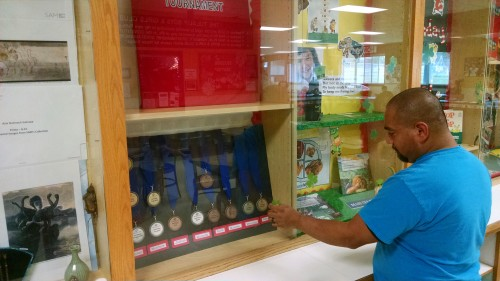 Jay Miranda, Tulalip Boys & Girls Club games room director stands in front of the special display that houses the medals won in the March 7, 2015 Boys & Girls Club of Snohomish County Games Tournament. (Tulalip News Photo/ Brandi N. Montreuil)