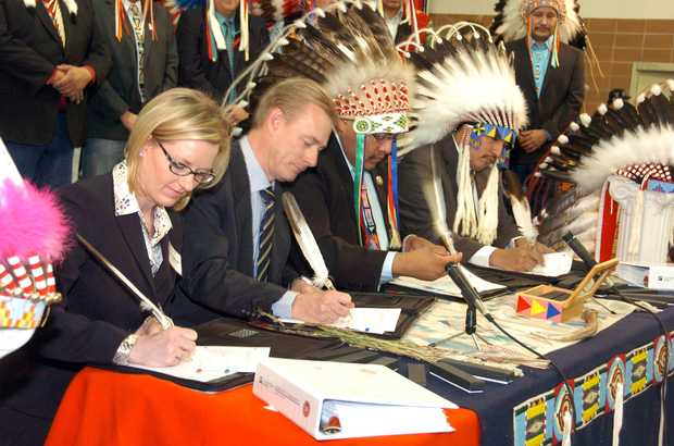 Representatives of Cloud Peak Energy and Montana's Crow Tribe sign an agreement Thursday Jan. 24, 2013, that gives the mining company leasing options on 1.4 billion tons of coal beneath the Crow Indian Reservation, in Billings, Mont. Pictured from left are Cloud Peak legal counsel Amy Stefonick, company chief executive Colin Marshall, Crow Tribal Chairman Darrin Old Coyote and Tribal Executive Secretary Alvin Not Afraid. The deal would expand mining on the reservation with the coal likely to be exported overseas. MATTHEW BROWN — AP