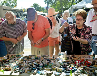 Shoppers look at Zuni fetishes at last year's Indian Market on Santa Fe's Plaza. Many Native American artists earn a substantial portion of their income during the two-day event. (Marla Brose/Albuquerque Journal)