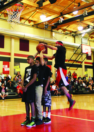 Kenny Dobbs performs his aerial display, wowing everyone in attendance by dunking over several community members.Photos/Micheal Rios
