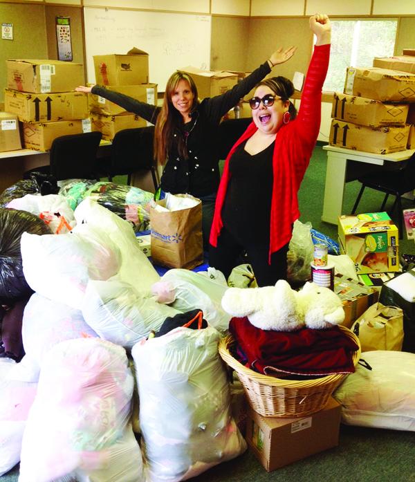Katie Jones and Jennifer Cordova-James among a heap of donations gathered for Pine Ridge Reservation residents.Photo/Kim Kalliber