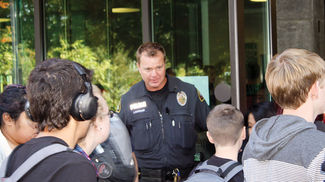 hristopher AnderssonMarysville School Resource Officer Chris Sutherland holds a door open for students at Marysville Getchell High School during a passing period on Oct. 1.